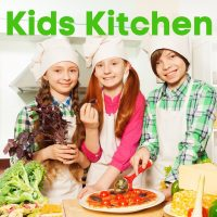 Two female and one male pre-teen in bright tops wearing chefs hats and aprons. The two girls are holding a purple leafed vegetable and the boy is cutting a pizza