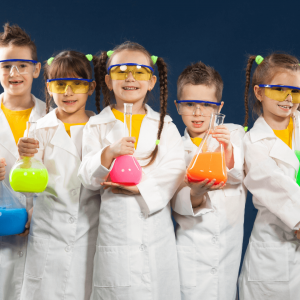 Five children wearing yellow tops and long white labcoats with safety glasses holding onto large beakers with different coloured liquids