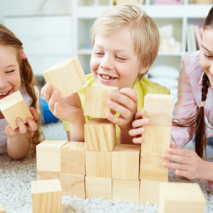 a blonde boy in the centre of the image with two girls only partially in frame all playing with tan builing blocks with smiles on their faces
