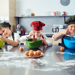 Three children wearing chefs hats and aprons whisking ingredients in coloured mixing bowls. The bench is covered in flour and egg shells