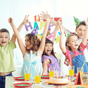 Five colourfully dressed children waving their arms in the air at a birthday party